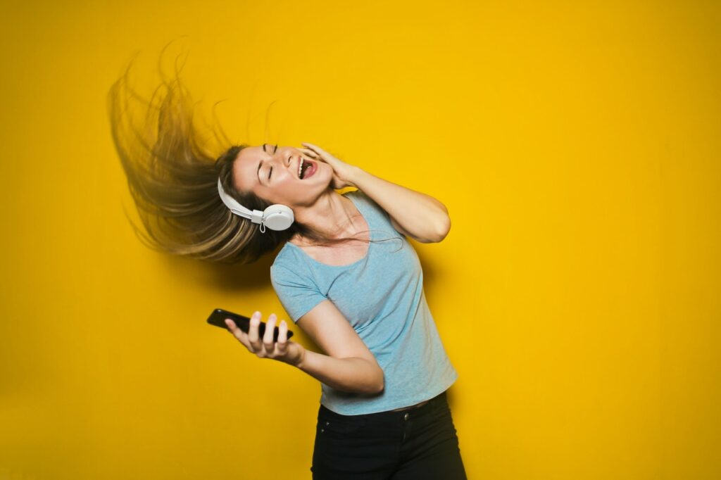 woman dancing with white headphones in front of yellow background to workout playlist