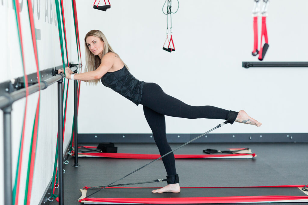woman wearing all black workout attire stretching her leg behind her using BOARD30 bungee system while leaning up against the wall