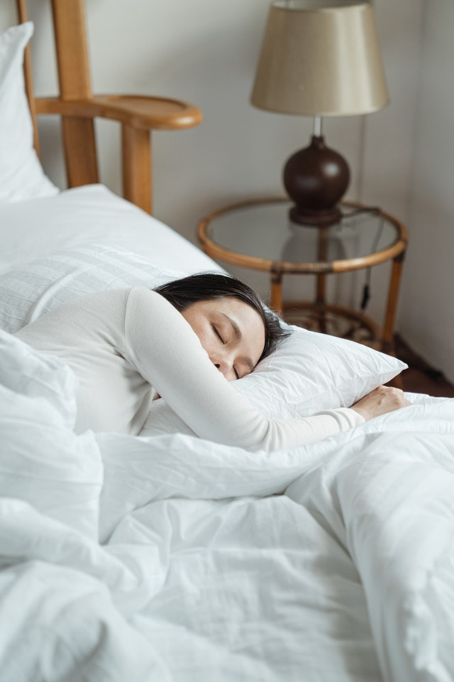 woman sleeping in bed of white blankets to recover from exercise