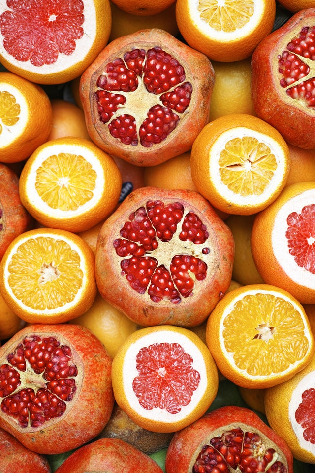 a mix of oranges and pomegranates combined sliced in half so you can see their seeds
