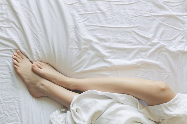 woman's feet in bed on white sheets and bedding