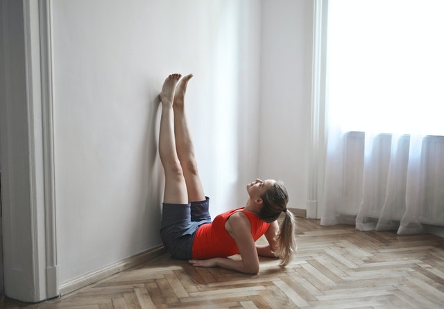 woman in workout gear resting up on her elbows with legs straight up against the wall